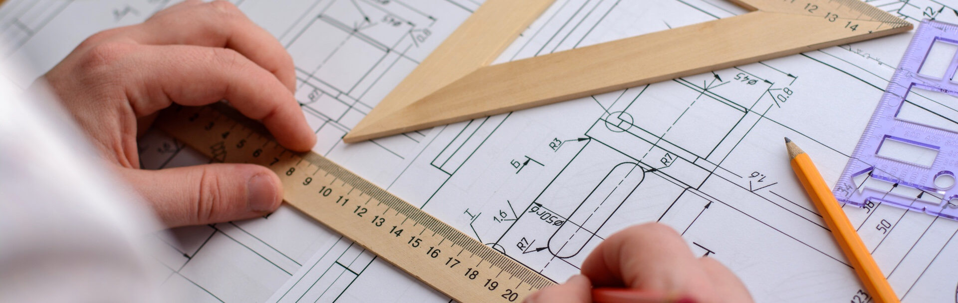 Engineer looking at product blueprints with rulers on top