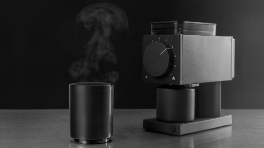 Fellow Ode Coffee Grinder on table with cup of coffee