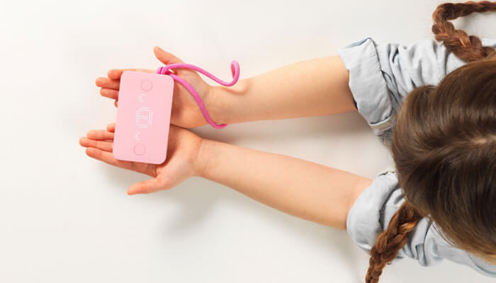 Child holding pink Pigzbe crypto storage wallet